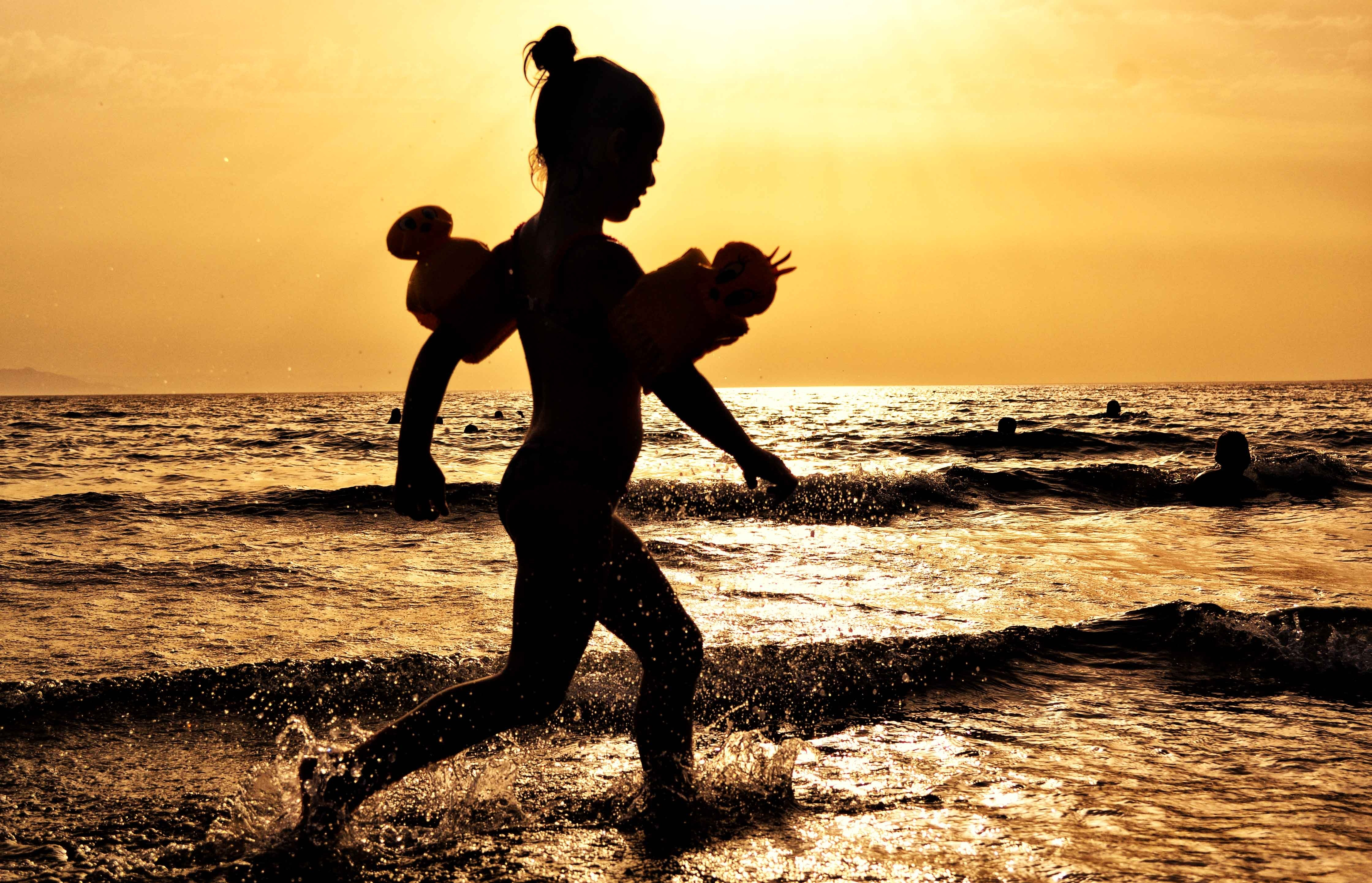 young girl in the surf at sunset