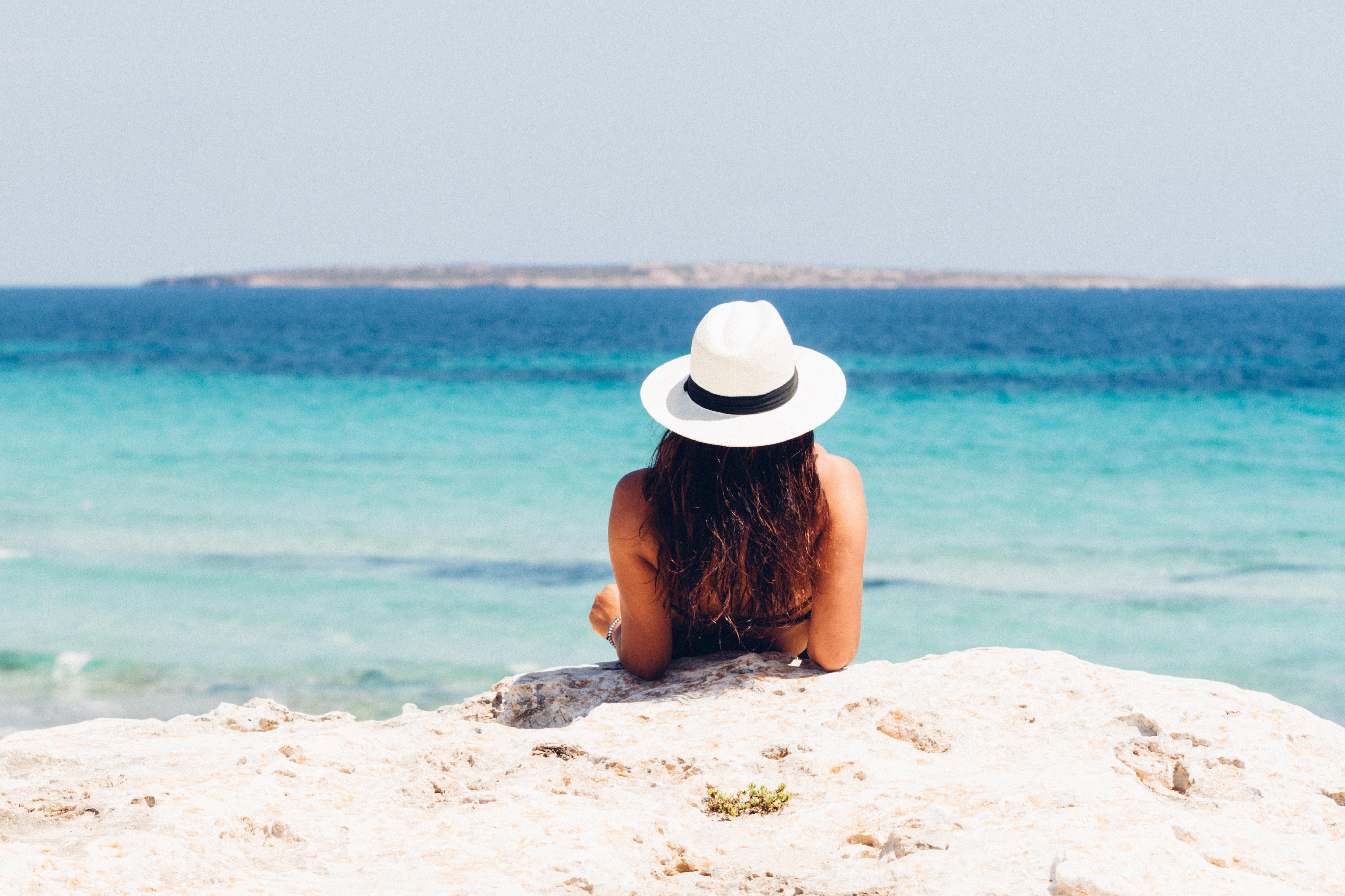 Woman lying on a beach wearing a white sun hat