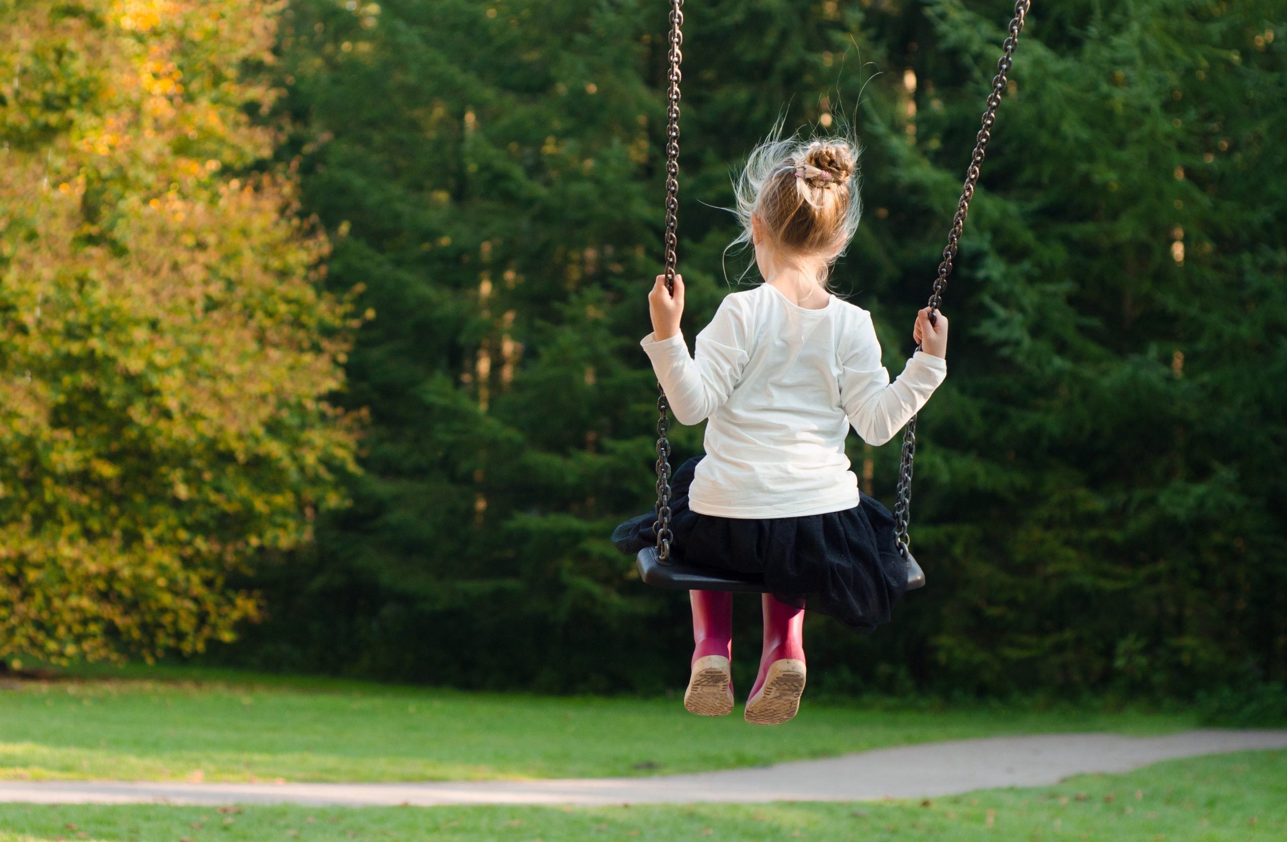 young girl on outdoor swing with green trees
