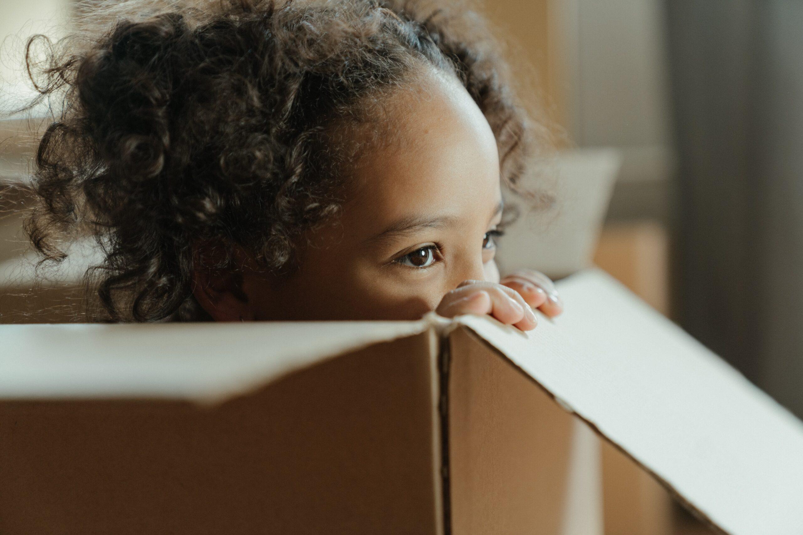 young girl playing in cardboard box
